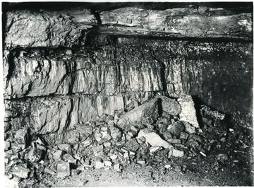 "'Probably no phase of coal preparation requires the supervision and care that must be given to shooting practices. The type of explosive used is a safety powder known as ""Duobel"" and has been selected because it is most suitable for the coal mined in the White Oak Mines. Not only must the explosive be of the best quality and best suited for the work of breaking down the coal, but its use must be supervised and restricted. The proper amount to use; the size of the cartridge; the manner of tamping and many other details are looked after so that a maximum of lump and coarse coal is produced after shooting. This view shows the working place after the 'breaker shot' has been fired.'"