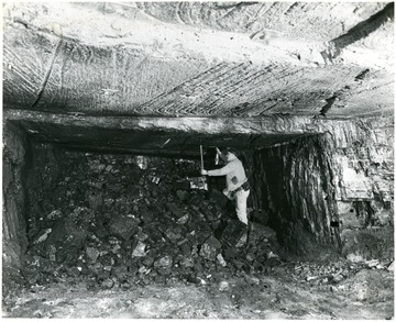 Miner works on pile of shot down coal.