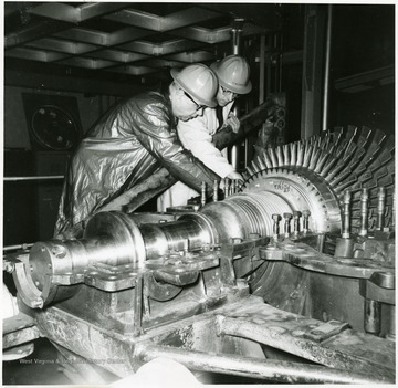 J.P. McGee, Acting Research Director, and Jack Smith, in Charge of the Gas Turbine Development Project discuss proper positioning of the turbine rotor in its casing.