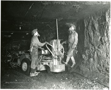 Miners using a machine to bolt the mine roof.