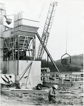 Two men working with cables while a crane is being used in the background.