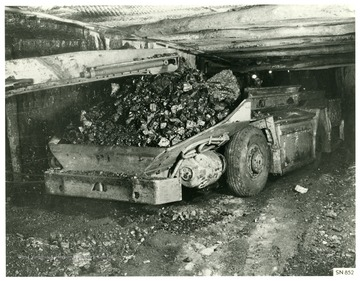 Miner operates a shuttle car that is loaded with coal.