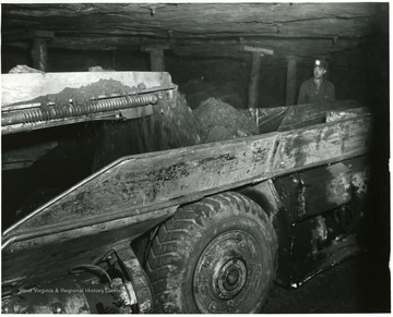 Minre watches as coal pours into the shuttle car.