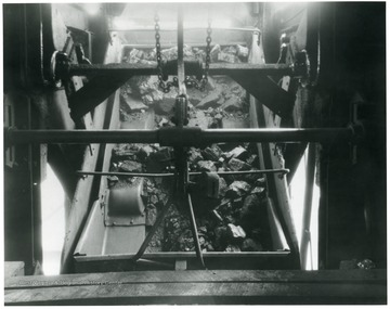 'Coal at all White Oak shafts mines is handled on self dumping cages, which handle the coal uniformly and with a minimum of breakage. Note how evenly the coal is flowing from the mine car. Much more rapid of course than the picture indicates, but it shows how well designed the equipment must be to handle the coal in such splendid manner.'