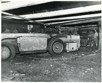 Miner watches as coal loads into a shuttle car.