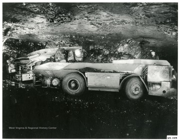 Shuttle car in an underground mine, loaded with coal.