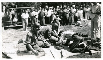 Group of men rehearsing mine safety procedures on a practice victim.