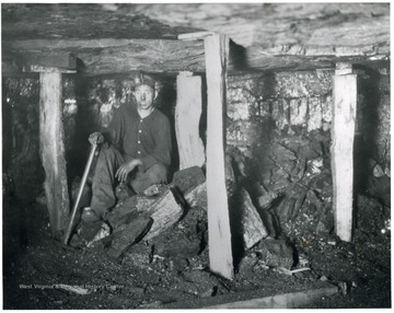Miner sitting in between posts that hold the roof of the mine up. 'Safety First is stressed in every possible way at White Oak mines.  Note the posts to protect this man at his labor.  He is waiting for another mine car so he can clean up his working place and make it ready for the mining machine crew who will cut it during the night, ready for him to work tomorrow.'