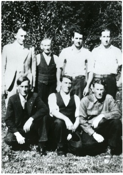 'Top Row. On left in light suit Fred Mooney; Next, the little man, our Dad, Watt Mooney; Next to Dad, me, John Mooney; far right standing Earl Mooney. Bottom Row. Left, Ira Mooney, center, Earnest Mooney, Right Rufus Mooney; all sons of Watt Mooney and brother to Fred Mooney. One brother missing, Oather Mooney. You will find him in other pictures.
