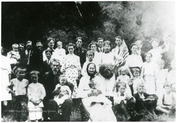 Group portrait of the Mooney family. 'This picture was taken in August, 1908. See ink mark on Big Woman. This is my mother. My father holding me next to Mom. The two old folks sitting at bottom are my Grandfather and Grandmother, Alfred Mooney and Liz, his wife, son of Ralph Mooney.' Note, negative cropped too close.