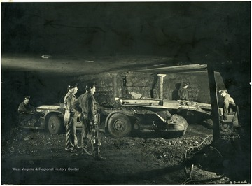 Miners operating a cutting machine.