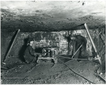 Two miners work with a machine to undercut coal.