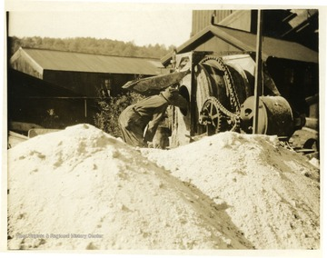 A miner working with machinery on the exterior of a mine.