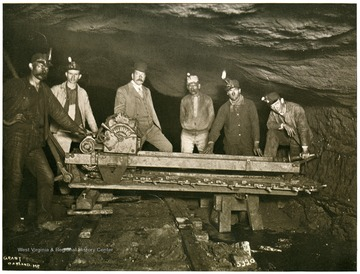Six miners pose by a electrical cutting machine in a mine in Preston County.