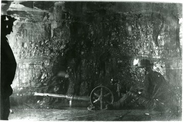 A miner works on a piece of machinery on the interior of the mine. John Williams, Coal Life Project.