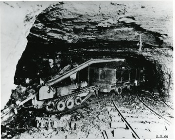 Miner working with a loading machine. 'Compliments of Joy Manufacturing Co.'