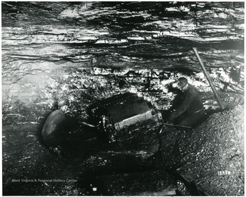 Two miners work with a mining machine. 'Compliments of Jeffrey Manufacturing Co.' John Williams, Coal Life Project.