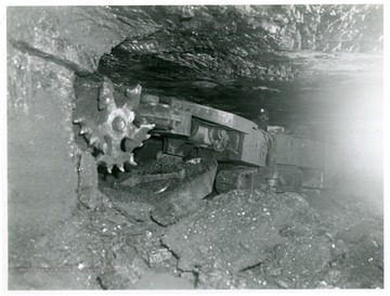 Miner using machine to cut coal.