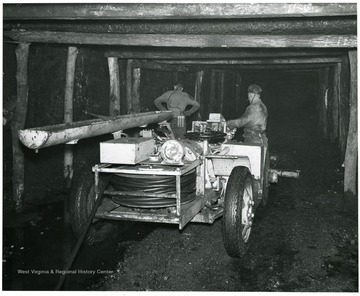 Two miners standing next to drilling machine.