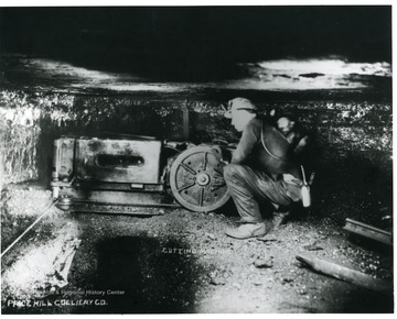 A miner is operating a cutting machine at the Price Hill Colliery Co. mine