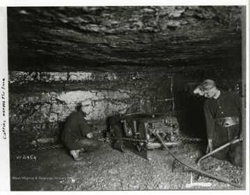 Two miners using a machine to cut across the face of a wall in a mine.