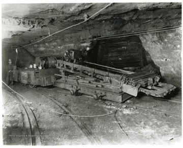 Miner with a large machine in the Pocahontas Mine.