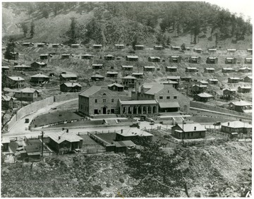 Coal town with Company building in the center. Sign on front of building says 'Safety The First Consideration.'