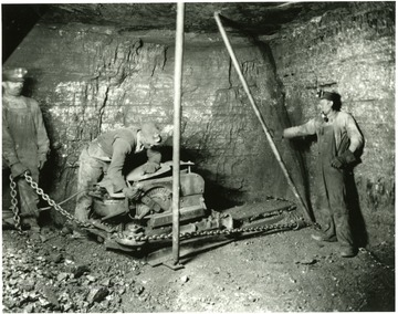 Three miners work on a piece of machinery at Elkhorn, W. Va.
