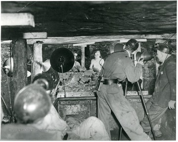 'Scene from a coal mine 300 ft. under a mountain in W. Va., where W.E. Austin, movie cameraman for the Norfolk and Western RR is shown taking what are believed to be first color movies inside a mine.'