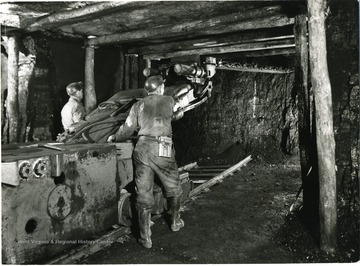 Two miners operate a cutting machine. 'Credit must be given to Willaim Vandivert, 21 East Tenth St., New York 3, N.Y., Not to be reproduced without written liscense.'