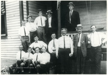 Portrait of men standing on and around a porch.