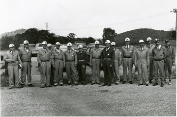 Men in suits with coveralls over top of them wearing hardhats and head lamps.