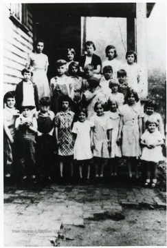 Group portrait of students standing on steps outside of school.