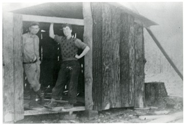A view of two men standing by tool storage.