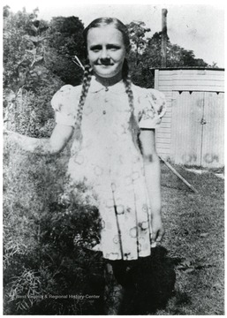 Mike Viola's Daughter, Rita, at about 7 or 8 years standing in a garden.