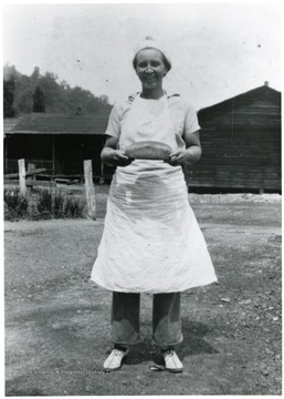 Woman holding loaf of bread.