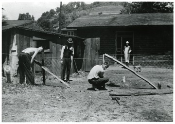 Two men performing maintenance work, other two are visible in the background.
