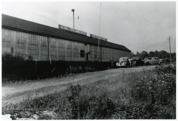 Men with cars outside of a National Youth Administration Building used as a salvage building.