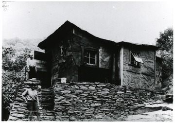 Picture of two men standing in front of a house.