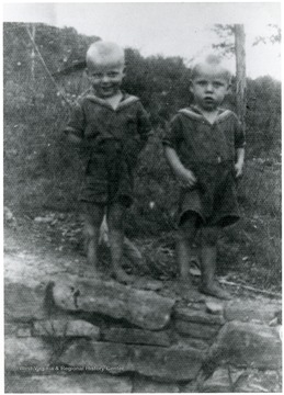 Two boys stand on a rock wall. 'Gloomy and Bonnie's.'