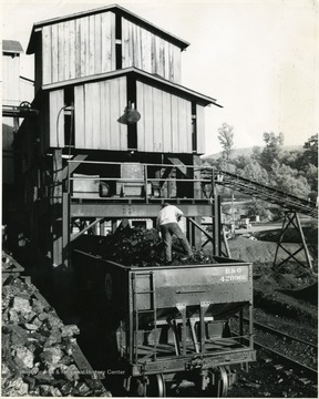 A man stands atop a filled coal car. 'Loading coal into railroad gondolas is made easy by structures called 'tipples.' The pictured tipple is typical of those to be found throughout the rich bituminous coal fields of southern West Virginia.'