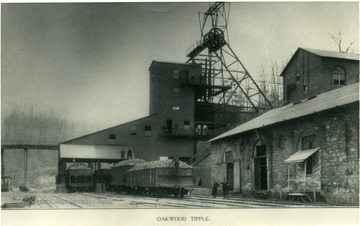 Oakwood Steel Tipple loading coal cars.  Men standing on the coal in the cars.