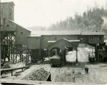Coal car under a tipple.  Men with horse drawn carriage also going under the tipple.