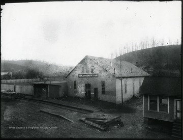 View of Glen Jean Athletic Club building and nearby dentist's office. 'Near Treveys Studio. Trevey's negatives were stored in the attic of this building after he closed his studio. McKell Ballfield on left, famous for a type of softball called Letemhitit.  Insurance agency on right operated by James Long.  Railroad is the K. G. J. [and] E. (Kanawha, Glen Jean, and Eastern). Athletic building contained a pool room, bowling alley, etc.'