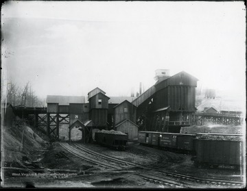 Filled railroad cars at the Collins Colliery Tipple. There is a water reservoir in the background.