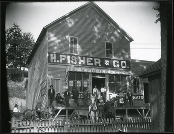 Men, women, and children standing in front of the H. Fisher and Co. Store.  Horse drawn carriages are also in front.