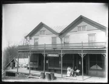 Family sitting in front of the Moravics and Co. building which also houses a general merchandise store.