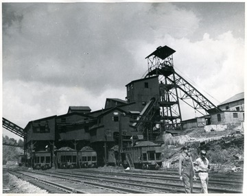Two men walking away from either Cranberry or Summerlee tipple loading coal cars.