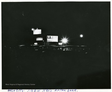 View of lights, signs, and cars parked at the I.B.E.W. Headquarters in Oklahoma City after dark.