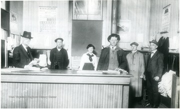 'Interior of Chesapeake [and] Ohio Railroad Freight Depot at Alderson W. Va. At extreme left, behind counter is the station agent T.L. Dameron and standing on extreme right is freight agent W.A. Hancock (who worked in the Alderson station for fifty years. He was a deaf-mute.)'